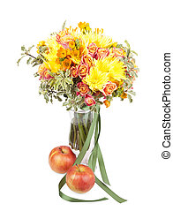 Bunch of spring flowers in a vase with apple isolated on white background