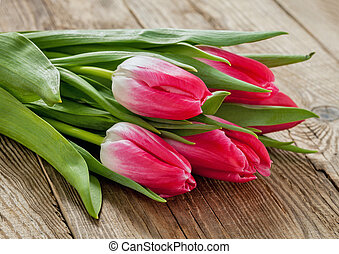 Bunch of spring tulips on an old board