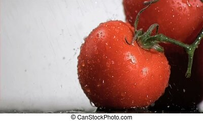 Bunch of tomatoes in super slow motion being sprayed with water