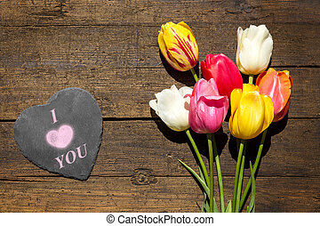 Bunch of tulips on a wooden background, slate with word i love you