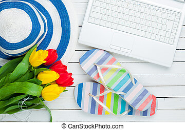 bunch of tulips, sandals, hat and laptop on the wonderful white wooden background