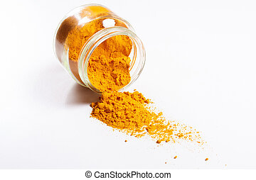 Bunch of turmeric spilled from glass jar.