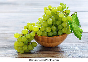 Bunch of white grapes in a wooden bowl.