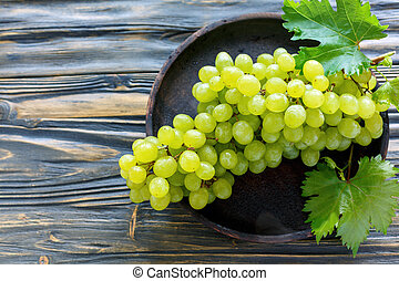 Bunch of white grapes on a wooden dish.