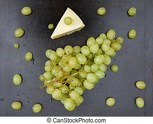 Bunch of white seedless grape and a piece of cheese