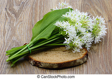 bunch of wild garlic on slice of bread at table. top view