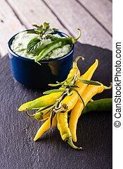 Bunch of yellow and green chili pepers with wasabi dip in blue bowl