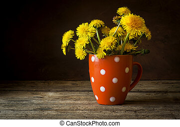 Bunch of yellow dandelions in vase on vintage wooden table