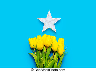 bunch of yellow tulips and beautiful star shaped toy on the wonderful blue background