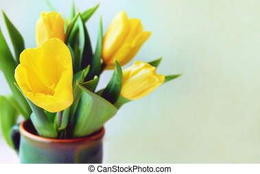 Bunch of yellow tulips in ceramic vase on a window.