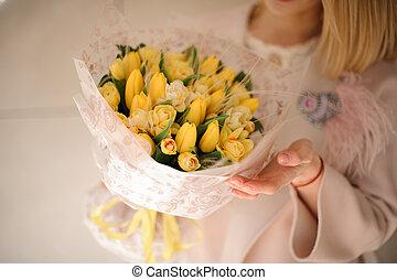 Bunch of yellow tulips in girl's hands