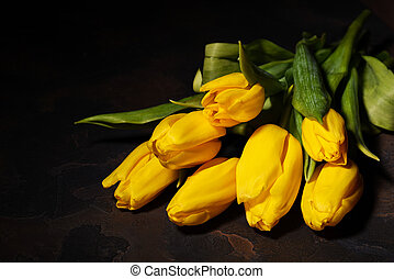 Bunch of yellow tulips on a dark background.