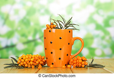 Bunches and cup of sea buckthorn berries on green abstract.