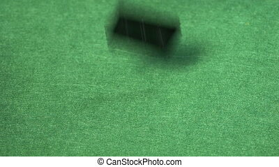 Bunches of black domino tiles falling on empty table