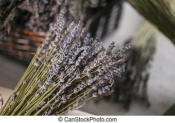 bunches of dried lavender in backet on wooden background.