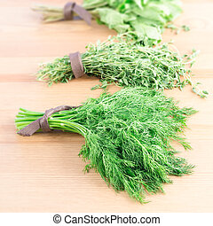 Bunches of fresh dill,  thyme, mint and parsley on a light wooden background