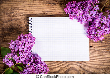 Bunches of lilac on old table with blank notebook