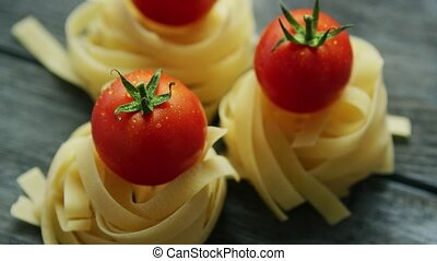 Bunches of pasta with wet tomatoes - Closeup of arranged raw...