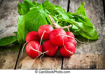 bundle of bright fresh organic radishes with leaves on wooden table