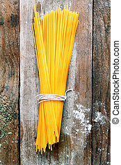 Bundle of Italian spahgetti pasta tied with string lying on...