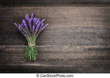 bundle of lavender flowers on on vintage wooden background
