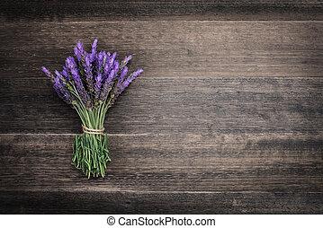 bundle of lavender flowers on on vintage wooden background