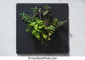 Bundle of Mediterranean herbs for cooking on a black slate plate