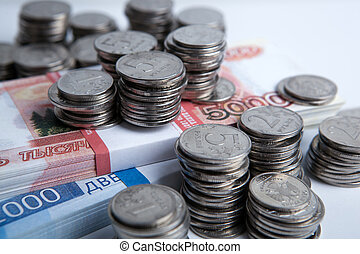 bundle of russian banknotes and many Russian coins