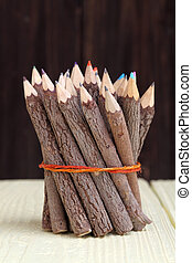 Bundle of tree trunk pencils on wooden table