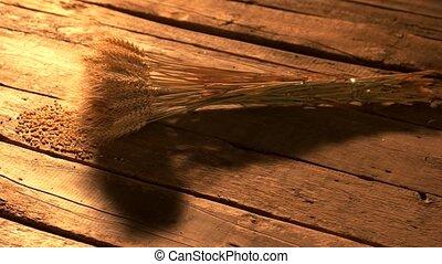 Bundle of wheat ears on wooden boards. Sheaf of dried golden...