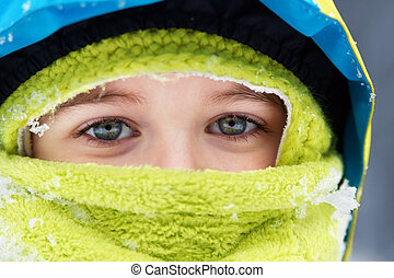 Closeup of bundled up blue eyed little boy with snow flakes details