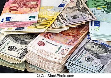 Bundles of money in three currencies