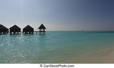 bungalow huts in sea on tropical resort beach