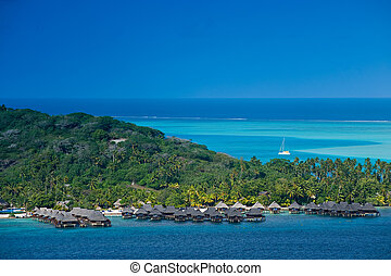 Bungalows sitting over the turquiose lagoon in Tahiti - View...