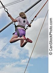 A young girl enjoys a bungee jump at an outdoor festival