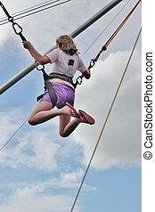 Bungee jumper - A young girl enjoys a bungee jump at an...