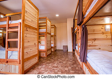 Bunk wooden beds in the hostel. Personal lighting over each bed.