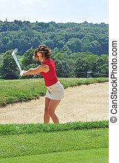 Bunker Downswing - Lady golfer executing a bunker shot