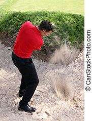 Bunker Shot - Young golfer hitting a shot out of a bunker