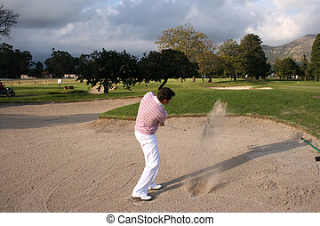 Bunker Shot - Young golfer playing out of the bunker, sand...
