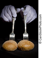Buns on the forks and hands in white gloves