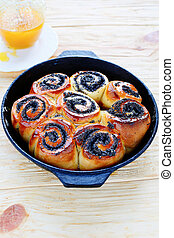 buns with poppy seeds in a frying pan
