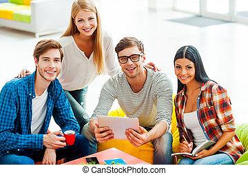 buono, squadra, è, uno, chiave, a, success., gruppo, di, felice, giovani persone, lavorare insieme, mentre, seduta, in, il, zona resto, di, loro, ufficio