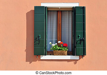 A closeup of a window on a colourfully painted house on Burano island in the Venetian Lagoon, northern Italy.