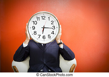 Businessman with alarm clock on head, studio shot.