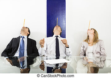 Bureau - Businesspeople balancing pencils on face in meeting...