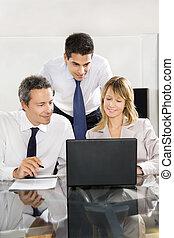 Businesspeople looking at laptop in meeting room.