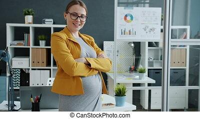 bureau, debout, femme affaires, portrait, jeune, traversé, sourire, pregnant, bras