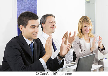 Bureau - Businesspeople clapping in business meeting.