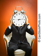 Bureau - Businessman with alarm clock on head, studio shot.